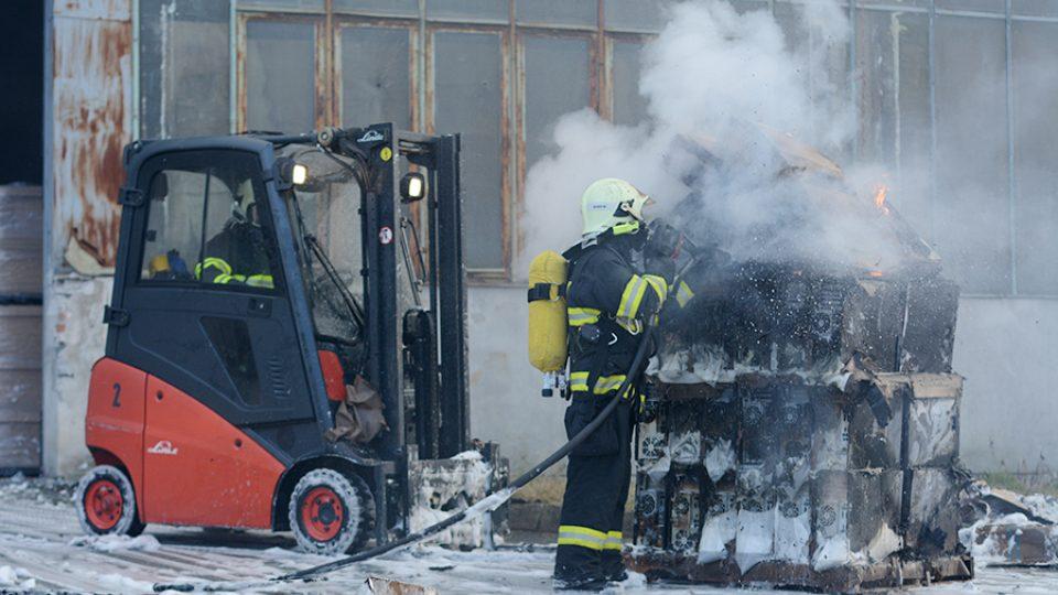 Hasiči zasahují u požáru haly v Černé za Bory - nejdříve musí hořící krabice vyvézt, následně je dohašují