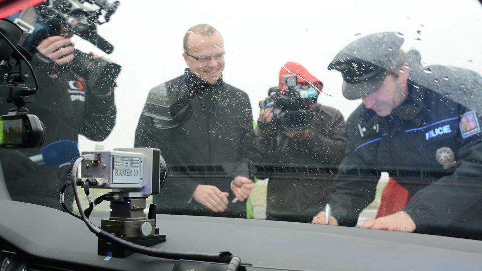 Ředitel policie Pardubického kraje Jan Švejdar přebírá vůz od hejtmana Martina Netolického pod dohledem dvou televizních a dvou policejních kamer