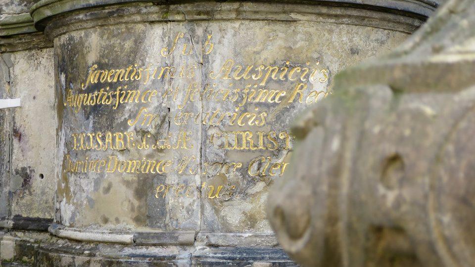 Latinský nápis na tamburu pod sochou sv Václava upomíná na záštitu císařovny Alžběty Kristiny