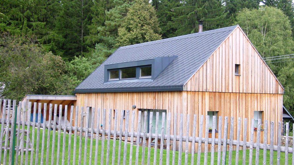 Soudobá moderní stavba v tradičních hmotách. Bezpřesahová střecha, bezrámová okna, oplechovaný pultový vikýř