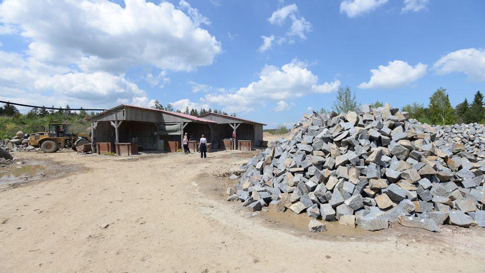 Bloky kamene pracovníci dopravují na přípravnou plochu nad těžební jámou