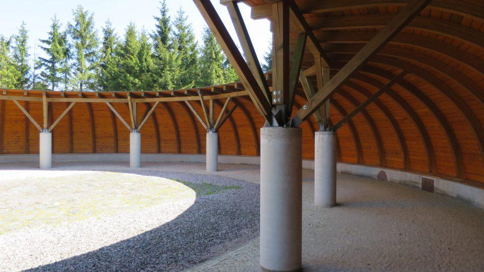 Dřevěný ochoz na úpatí rozhledny. V dlažbě je vyznačený půdorys někdejší dřevěné kaple
