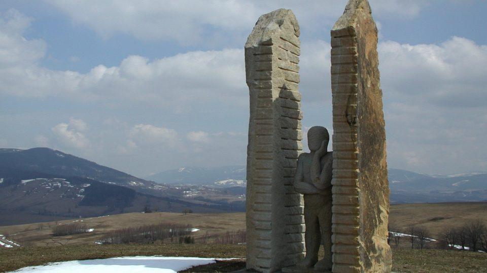 Socha Pozorovatele na Mariánském kopci vyhlíží směrem k západu. V pozadí pohoří Králícký Sněžník a Jeseníky