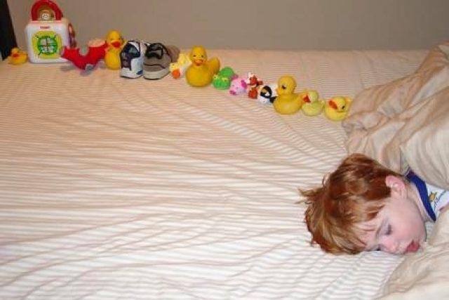 Spící autistické dítě s vyrovnanou řádkou hraček