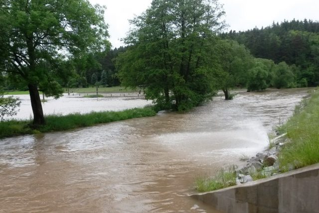 Rozlitá Klabava v Nové Huti na Plzeňsku. Na snímku vpravo je loni dokončený protipovodňový val, který odděluje řeku od obydlené části