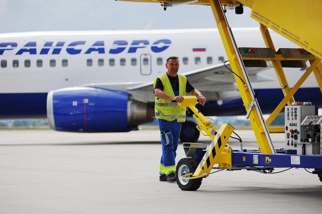 Technik na pardubickém letišti odváží schůdky od Boeingu 737