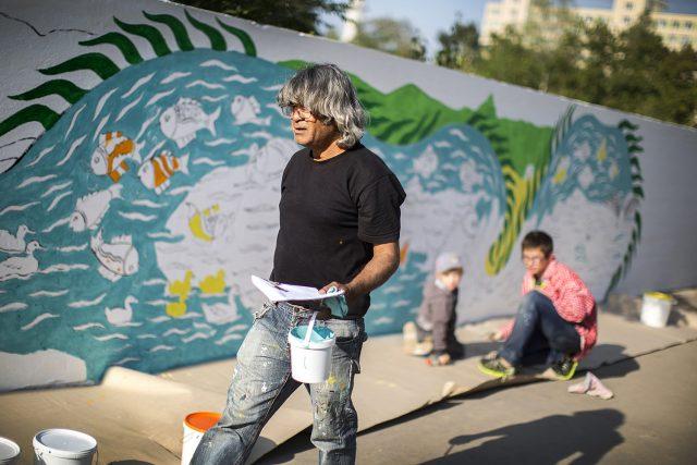 Bangladéšský malíř Ruhul Amin Kajol dohlíží na práci dobrovolníků