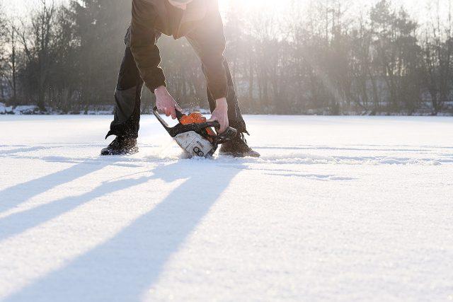Rybář vyřezává díru na rybníku Mazánek u Slatiňan. Led má tloušťku asi 20 cm