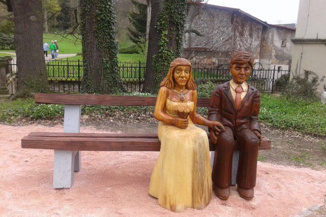 Dřevěné sochy na jedné z laviček symbolizují novomanžele