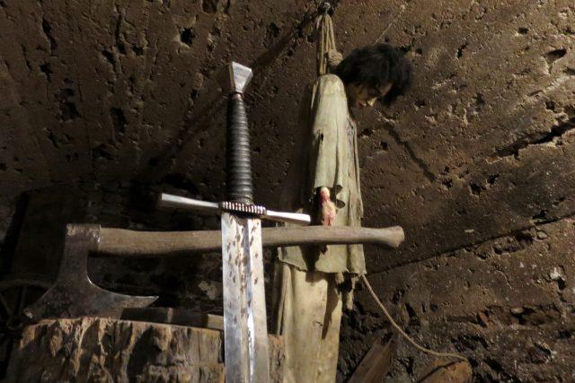 Figurina odsouzence a katovský meč v popředí