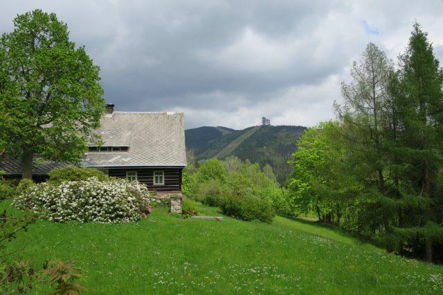 Roubená chalupa v částí Horní Morava, v pozadí Stezka v oblacích