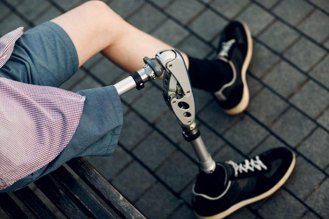 Mladý muž s protetickou končetinou odpočívá na lavičce
