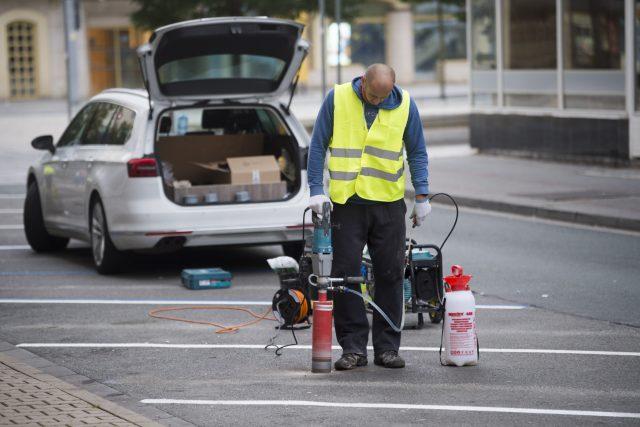Pracovník osazuje parkovací senzory v Pernerově ulici. Senzory budou základem inteligentního parkovacího systému