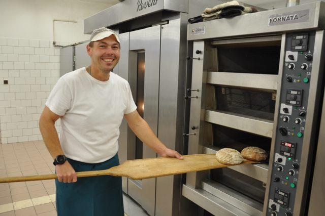 Pekař David Jeřábek vytahuje z pece upečený chléb