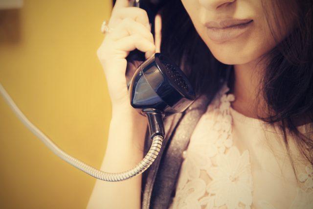 žena, telefonní sluchátko, starý telefon (ilustrační foto)