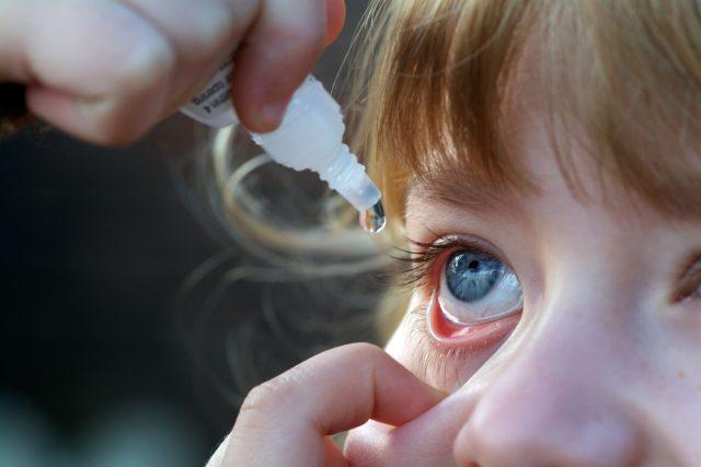 Rodiče vykapávají ditěti oči očními kapkami | foto: Profimedia