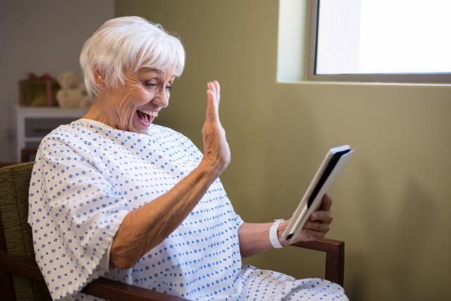 Starší žena v nemocnici používá tablet k videohovoru