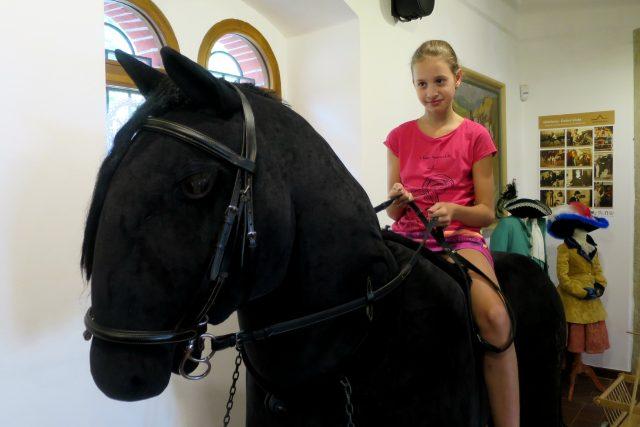 Největší plyšový kůň v Česku pod sedlem návštěvnice Interaktivního muzea starokladrubského koně ve Slatiňanech