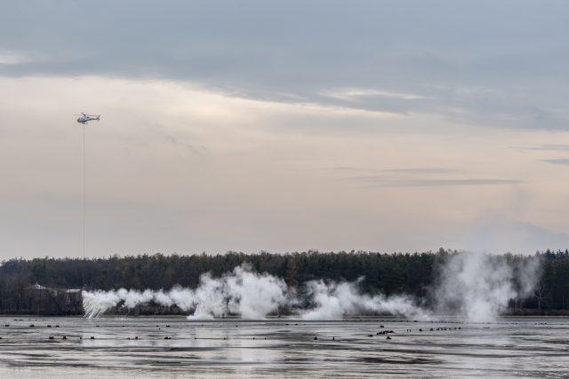 Specializovaná firma shazuje z vrtulníku na dno rybníka tuny nehašeného vápna