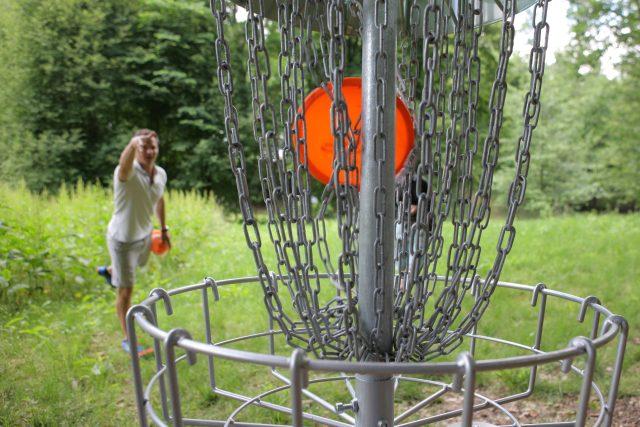 Koš na disc golf je potřeba správně trefit, řetězy by měly srazit disk dolů do koše